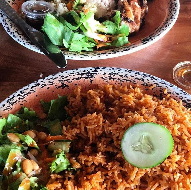 Jollof rice (rice cooked in tomato sauce and vegetables on the side) on a plate at a restaurant in Cape Coast, Ghana