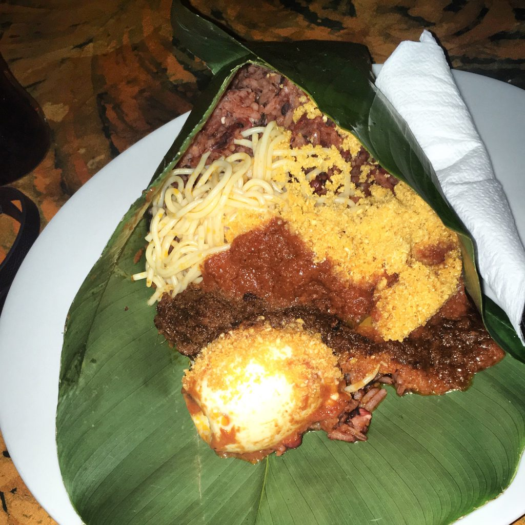 Waakye (rice, beans, spaghetti, egg and stew) packed in a plantain leaf. This is the traditional way of packing waakye in Ghana.